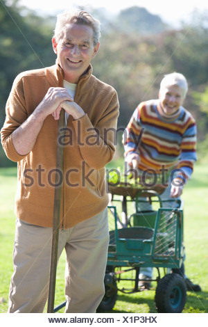 Portrait of smiling senior couple avec panier et d'outils de jardinage Banque D'Images