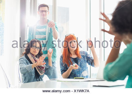 Angry woman throwing paper balls sur collègue in creative office Banque D'Images