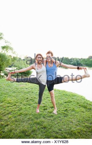 Couple practicing yoga par l'eau Banque D'Images