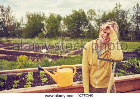 Femme mature, jardinage, appuyé sur le râteau, rire Banque D'Images