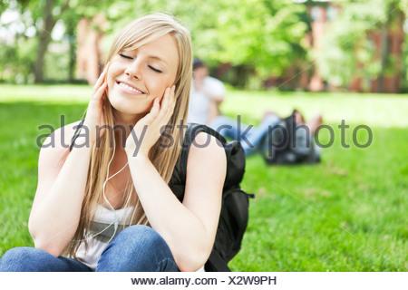 États-unis, Washington, Seattle, Woman listening to mp3 player in park Banque D'Images