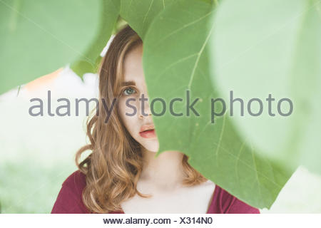 Portrait of a young woman with face cachée par des feuilles Banque D'Images