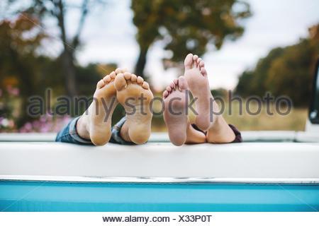 Jeune couple couché à l'arrière du camion, les pieds nus sur le bord du chariot, l'accent sur pieds Banque D'Images