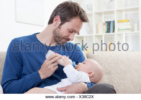 Germany, Bavaria, Munich, père de lait d'alimentation pour bébé garçon (6-11 mois) dans la salle de séjour Banque D'Images