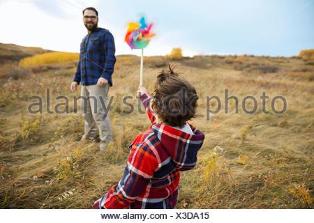 Père Fils regarder avec pinwheel in rural field Banque D'Images