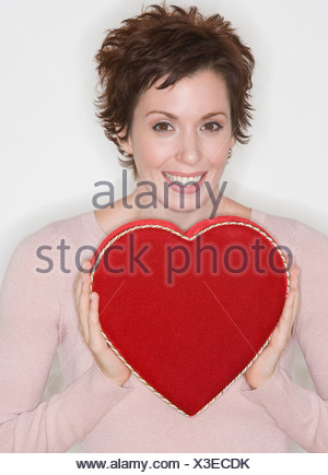 Woman holding heart-shaped box Banque D'Images