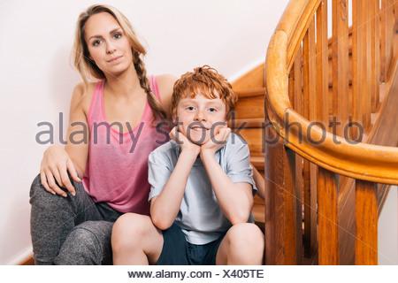 Portrait de mère et fils assis dans les escaliers de leur maison Banque D'Images