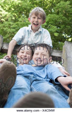 Trois amis s'amusant sur la diapositive en aire de jeux, Munich, Bavière, Allemagne Banque D'Images