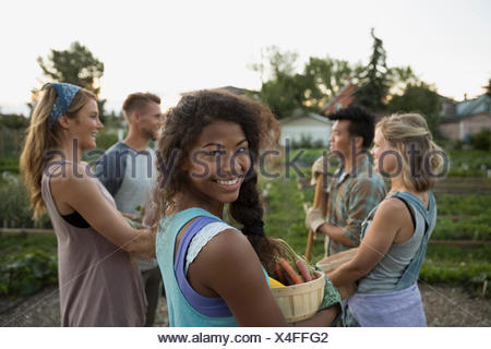 Portrait of smiling young woman with friends community garden Banque D'Images