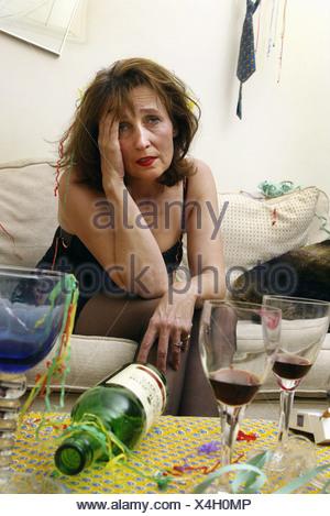 Le port de cheveux brune femme robe noire assis sur le bord du canapé se pencher en avant à la tête de la main à la misérable entouré par Banque D'Images