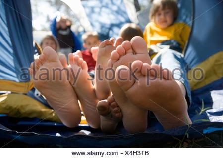 Vue sur les pieds des enfants poussant hors de la tente Banque D'Images