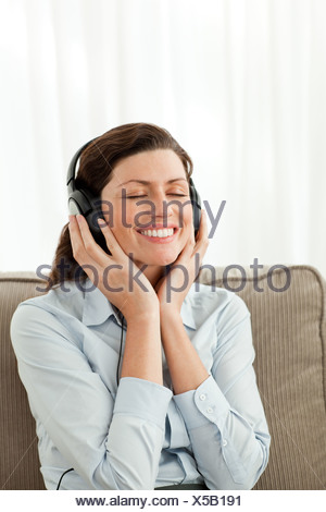 Cheerful businesswoman listening music Banque D'Images