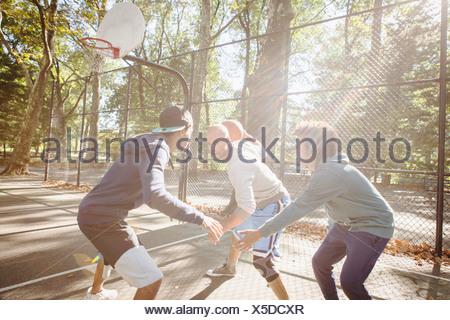 Les jeunes hommes jouant au basket-ball Banque D'Images