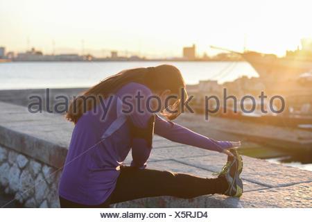 Jeune femme étend sa jambe sur un mur au coucher du soleil Banque D'Images