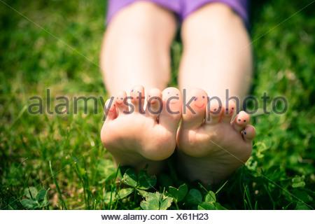 Petite fille avec les pieds orteils peints lying in grass Banque D'Images