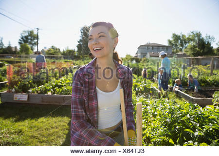 Smiling young woman tending sunny potager communautaire Banque D'Images