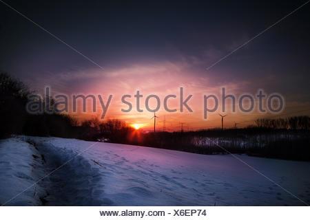 Silhouette d'éolienne pendant le coucher du soleil Banque D'Images