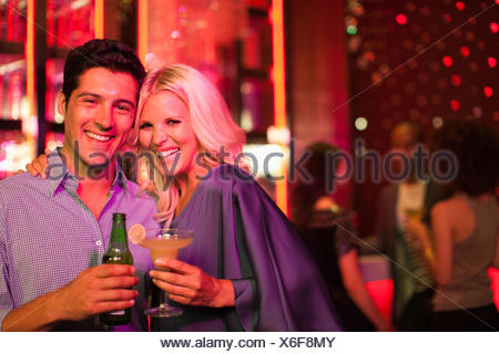 Couple holding drinks in nightclub Banque D'Images