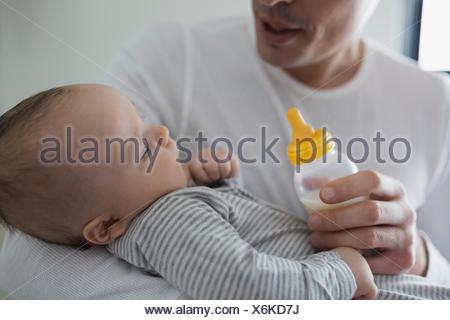 Père nourrir bébé garçon avec une bouteille Banque D'Images