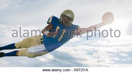 Les adolescents de sexe masculin American football player catching ball mid air contre ciel soleil Banque D'Images