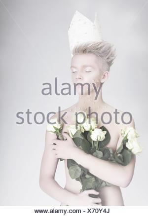 Le talent artistique. Jeune homme à la mode dans la couronne de fleurs en papier Banque D'Images
