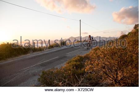 La France, la Corse, le cyclisme sur route au-dessus de la mer au coucher du soleil Banque D'Images