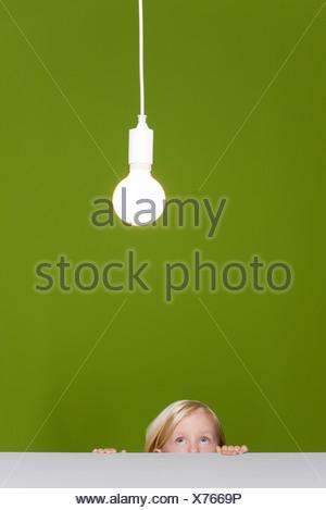 Petite fille à la créature jusqu'à l'ampoule lumineuse suspendue au-dessus Banque D'Images