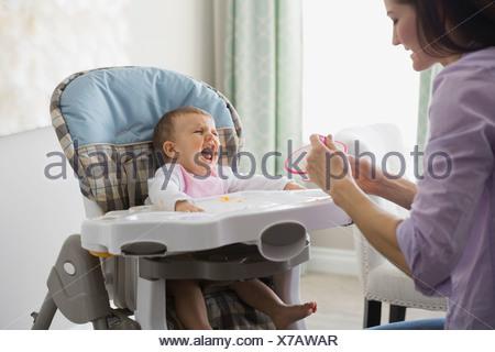 L'alimentation de la mère bébé qui pleure à la maison Banque D'Images