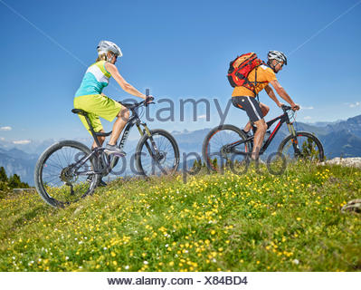 Homme Femme 40-45 ans et 35-40 ans avec des casques cycle avec leurs vélos de montagne, Zirbenweg, Patscherkofel, Innsbruck, Tyrol Banque D'Images