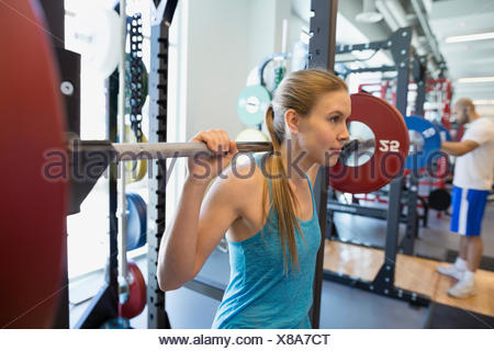 Woman doing squats barbell avec in gym Banque D'Images