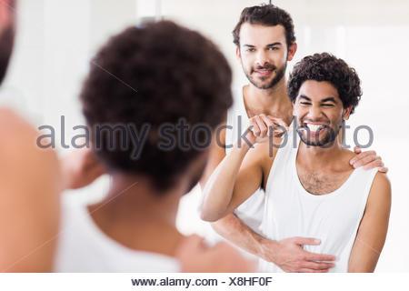 La réflexion de l'heureux couple gay dans la salle de bains Banque D'Images