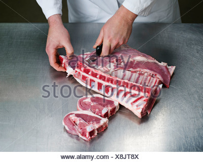 Un boucher découpant une viande Banque D'Images