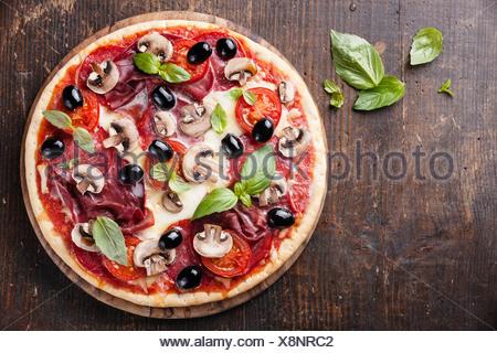 Italian Pizza au salami, les champignons et les olives sur la table en bois Banque D'Images