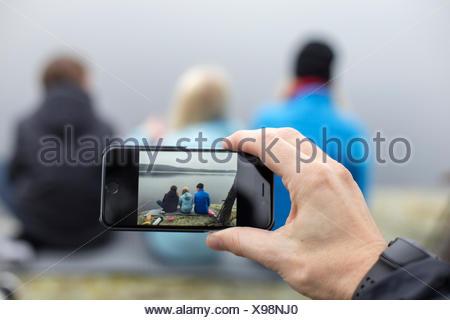 La Suède, Vastergotland, Lerum, Harskogen Harsjon, homme, prenant photo de femme avec deux fils (10-11, 12-13) avec smartphone Banque D'Images