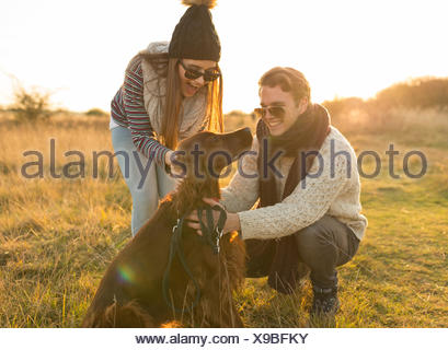 Jeune couple walking dog in field Banque D'Images