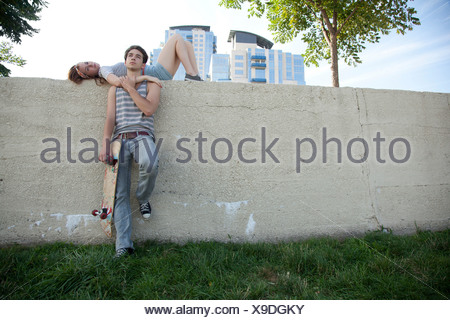 Jeune femme couchée sur mur avec la planche Banque D'Images