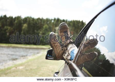 Woman in car, les pieds par la fenêtre ouverte, l'accent sur pieds Banque D'Images