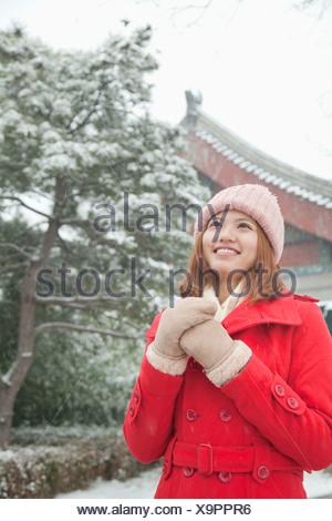 Jeune femme tenant les mains dans la neige Banque D'Images