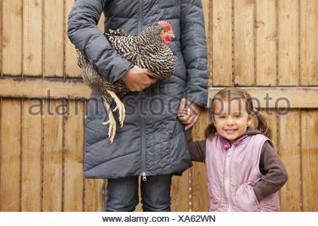 Une femme tenant un poulet noir et blanc avec une croix rouge coxcomb sous un bras une jeune fille à côté d'elle tenant son autre main Banque D'Images