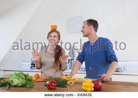 Young woman balancing poivron orange sur la tête. Banque D'Images