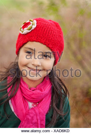 Girl (4-5) vêtu d'un tricot rouge hat smiling outdoors Banque D'Images