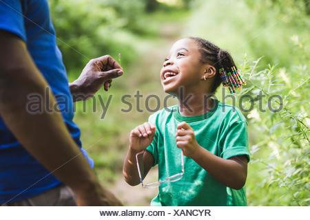 Père et fille à la recherche dans les usines de forest camp éco Banque D'Images