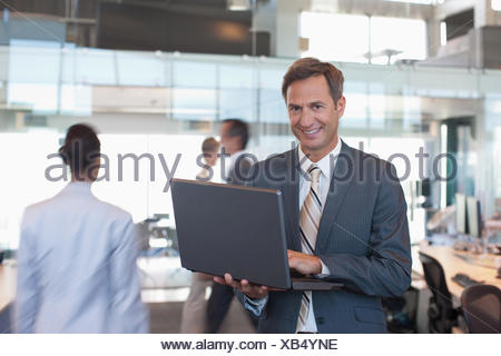 Businessman with laptop in office Banque D'Images