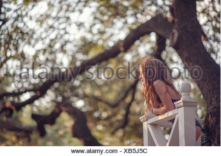 Girl leaning against wooden fence in backyard Banque D'Images