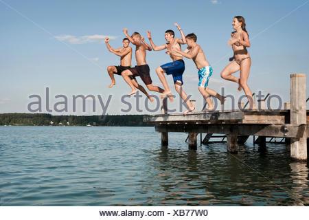 Cinq adolescents sautant d'une jetée dans le lac Banque D'Images