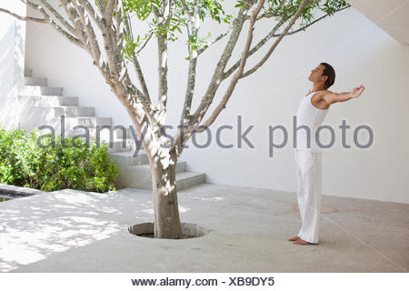 Man standing with arms outstretched in courtyard Banque D'Images