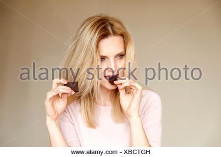Portrait de belle femme avec de longs cheveux blonds de manger une barre de chocolat Banque D'Images