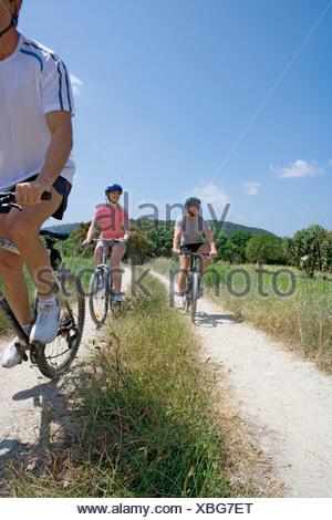 Men and woman riding bicycles sur chemin rural Banque D'Images