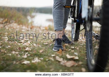 Jambes et Pieds de femme avec vélo dans les feuilles d'automne Banque D'Images