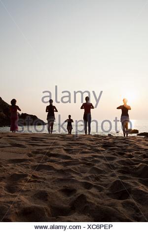 Les femmes pratiquant le yoga sur la plage au coucher du soleil Banque D'Images